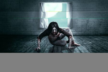 Scary zombies with blood and wound on his body crawling on the abandoned house. Halloween concept Imagens