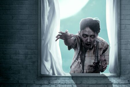 Scary zombies with blood and wound on his body haunted the abandoned house. Halloween concept