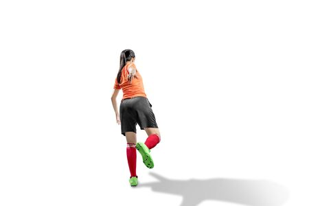 Rear view of Asian football player woman in the pose of kicking the ball isolated over white background