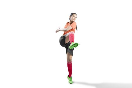Asian football player woman in the pose of kicking the ball isolated over white background Banco de Imagens