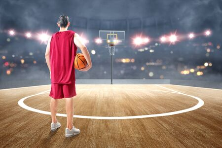 Rear view of Asian man basketball player holding the ball on his hand on the basketball court Standard-Bild - 129171307