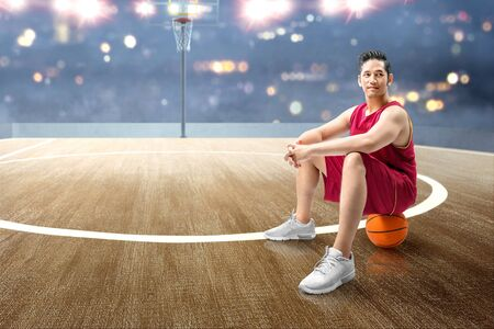 Asian man basketball player sitting on the ball on the basketball court Standard-Bild - 129171348