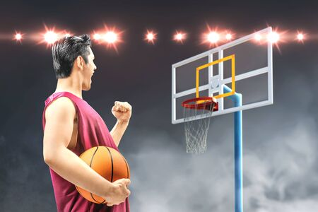 Rear view of Asian man basketball player holding the ball with an excited expression on the basketball court Standard-Bild - 129171344