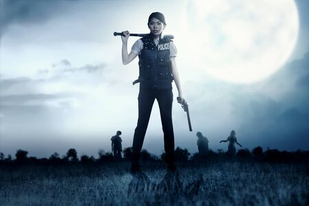Asian policewoman with the gun and baseball bat in her hand face the zombies on the grass field at night. Halloween concept Banque d'images - 129171834