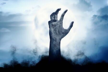 Levantamiento de la mano de zombies desde el suelo por la noche. Concepto de halloween