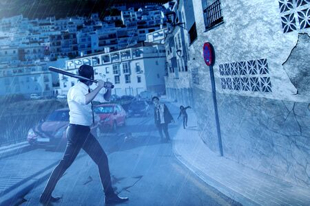 Asian businessman with a baseball bat on his hand face the zombies on the abandoned city at night. Halloween concept