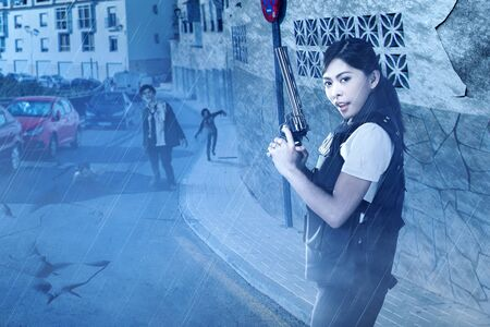 Asian policewoman with the gun on her hand face the zombies on the abandoned city at night. Halloween concept