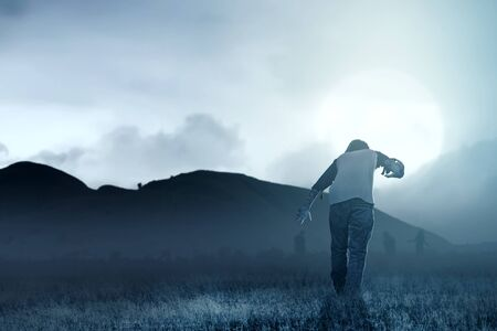 Scary zombies with blood and wound on his body walking around on the grass field with moonlight. Halloween concept
