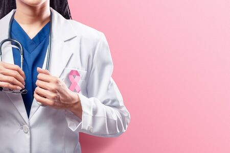 A woman doctor in a white lab coat holding a stethoscope on her hands with pink ribbon over pink background. Breast cancer awareness