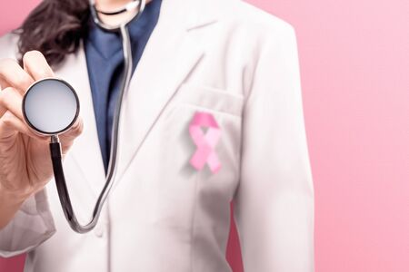 A woman doctor in a white lab coat using with pink ribbon using a stethoscope over pink background. Breast cancer awareness