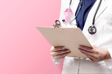 A woman doctor in a white lab coat with a pink ribbon and a stethoscope holding clipboard with a pink background. Breast cancer awareness Stock Photo