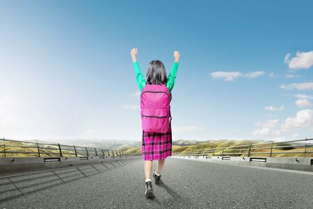 Rear view of Asian cute girl with a backpack and excited expression walking on the asphalt road with landscapes background Stock Photo