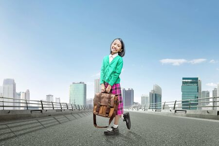 Asian cute girl with a suitcase and happy expression standing on the asphalt road with cityscape background Stock Photo