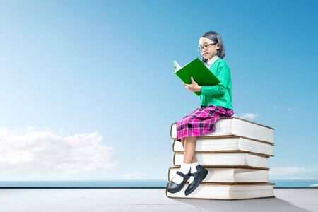 Asian cute girl with glasses sitting on the pile of books and read the book with a blue sky background Stock Photo