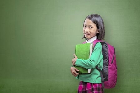 Asian cute girl with a backpack holding the book standing with a green background
