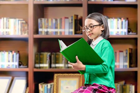 Asian cute girl with glasses sitting and read the book on the library Stock Photo