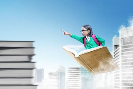 Asian cute girl with glasses and backpack sitting on book pointing forward while flying above the city