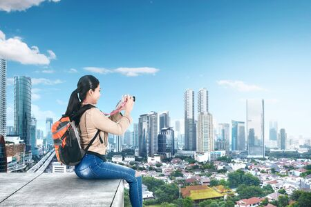 Asian woman with a backpack sitting on the rooftop and holding a camera to take pictures on the modern city