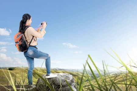 Rear view of Asian woman with a backpack holding a camera to take pictures on the green hills Stock Photo