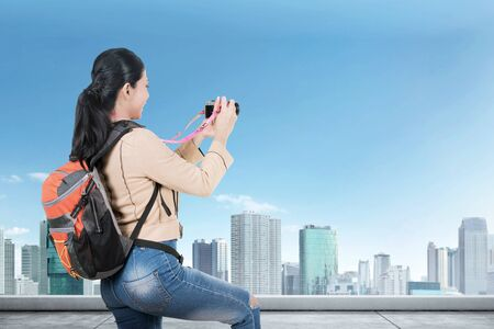 Rear view of Asian woman with a backpack holding a camera to take pictures on the rooftop of the building Stock Photo