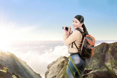 Asian woman with a backpack holding a camera to take pictures on the top of the mountain Stock Photo