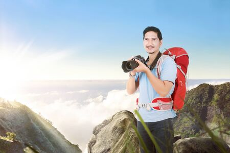 Asian man with a backpack holding a camera to take pictures on the top of the mountain