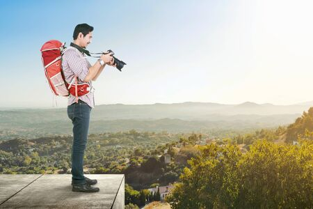 Asian man with a backpack holding a camera to take pictures on the green hills