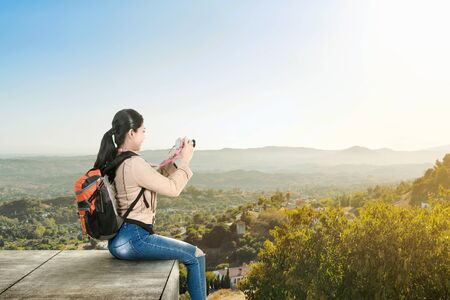 Asian woman with a backpack sitting on the rooftop and holding a camera to take pictures on the green hills