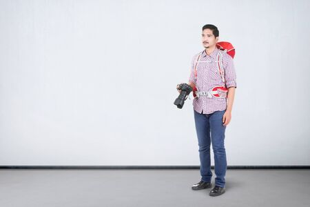 Asian man with a backpack holding a camera to take pictures over white wall background