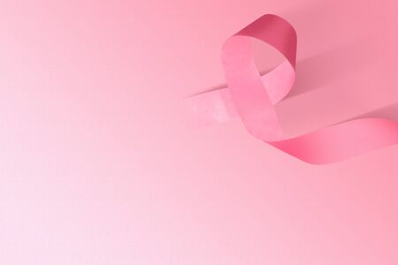 Pink awareness ribbon on a colored background. Breast cancer awareness