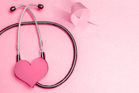 Pink heart and awareness ribbon with a stethoscope on a colored background. Breast cancer awareness