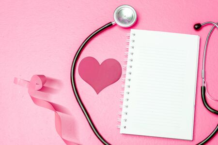 Pink heart and awareness ribbon with a stethoscope and empty book on a colored background. Breast cancer awareness Фото со стока