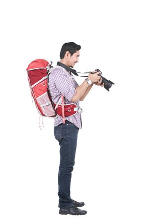 Asian man with a backpack holding a camera to take pictures isolated over white background