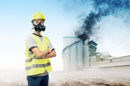 Asiatischer Ingenieur, der eine Schutzmaske verwendet, um ihn vor Luftverschmutzung aus der Industriefabrik auf dem Dürreland zu schützen