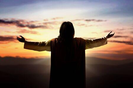 Rückansicht von Jesus Christus hob die Hände und betete zu Gott mit einem Sonnenuntergangshimmelhintergrund