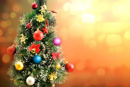 Decorated Christmas tree with colorful lights and ornaments over blurred lights background