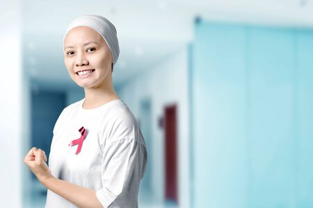Asian woman in a white shirt with a pink ribbon in the hospital background. Breast cancer awareness