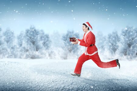 Asian man in Santa costume running while holding the gift box with snowy fir trees background Stock Photo