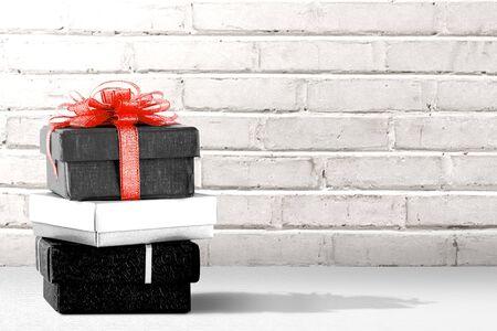 Stapel der Geschenkbox auf dem Tisch mit Wandhintergrund. Black Friday-Konzept