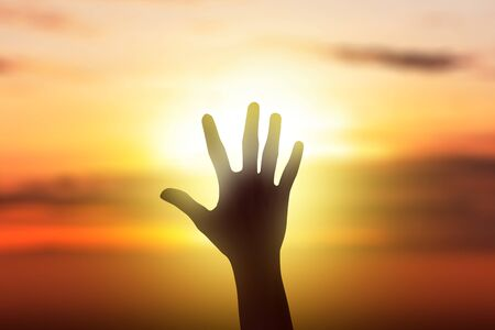 Human hands with an open palm facing sunset sky background 版權商用圖片