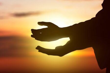 Sylwetka Jezusa Chrystusa modlącego się do boga na tle zachodu słońca na niebie Zdjęcie Seryjne