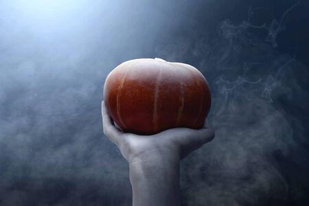 Hand holding pumpkin with dark smoke background