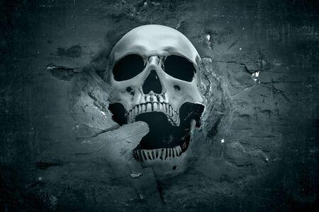 Menschlicher Schädel, der von einer rissigen Wand auf dunklem Hintergrund zeigt