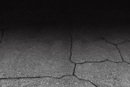 Cracked asphalt over dark background Imagens