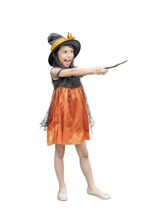 Asian girl in witch costume holding a magic wand isolated over white background