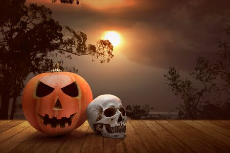 Jack-o-Lantern and human skull on a wooden table with a sunset sky background