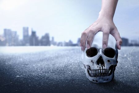 Hand holding human skull on the urban street with the night scene background