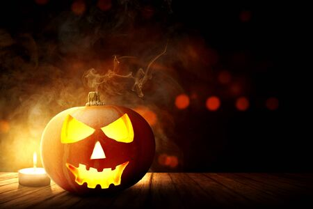 Jack-o-Lantern and candle on wooden table with dark background