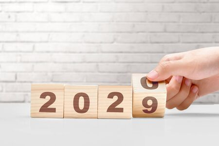 Hand changes the wooden cube from 2019 to 2020. Happy New Year 2020