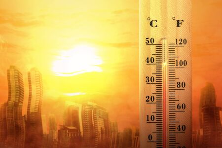 Thermometer with high temperature on the city with glowing sun background. Heatwave concept